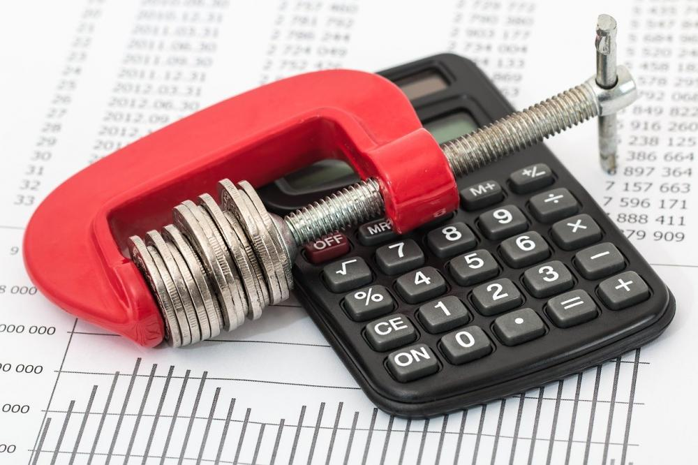 coins in a red clamp lying on a calculator for association learning management system cost concept