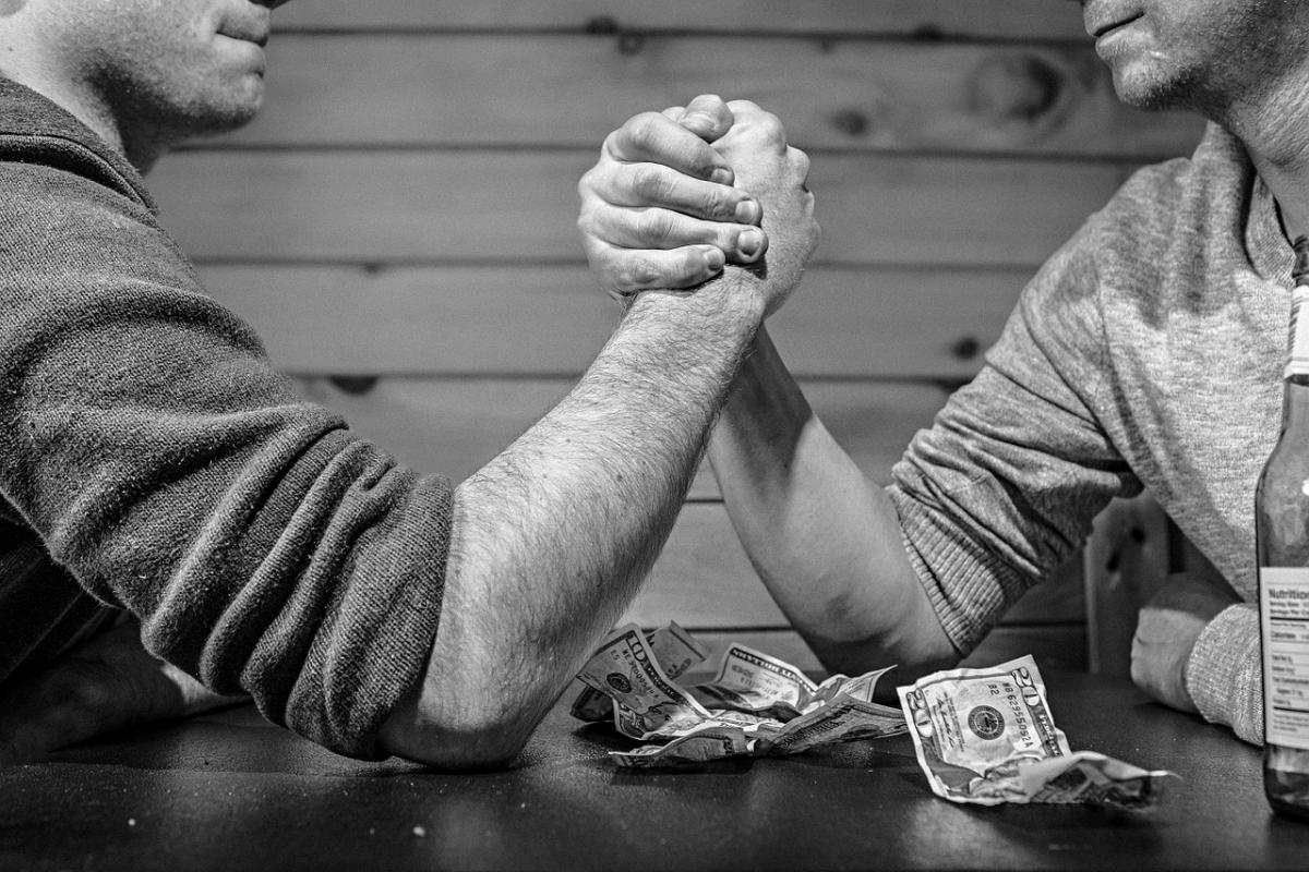 Two men arm wrestling - LMS vs. LXP concept